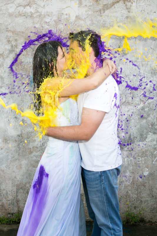 Kissing with paint being thrown at them