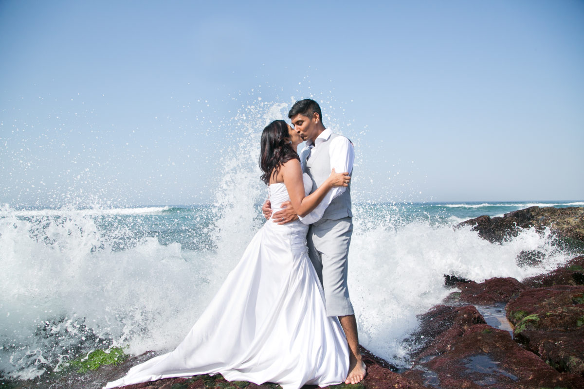 Groom and bride having fun in the water with a wave splashing off a rock behind them