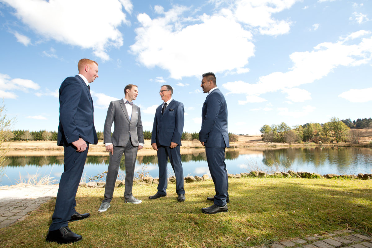 Groom and groomsmen standing in front of a lake