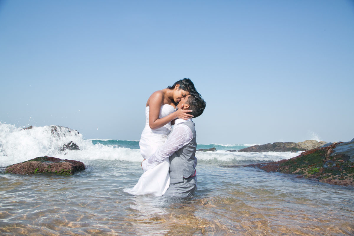 the bride and groom romantically having fun in the water with a wave approaching