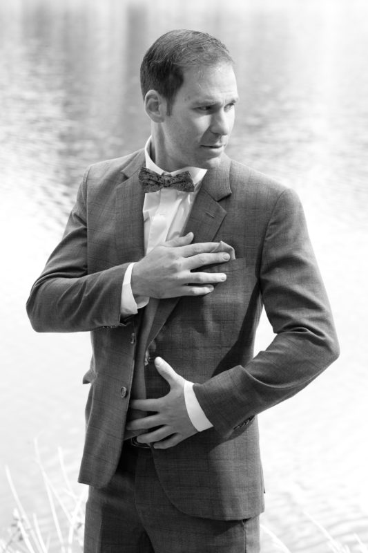 Groom in front of a lake in Black and White