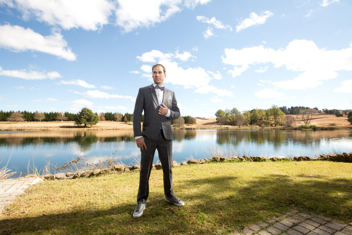 Groom standing in front of a lake