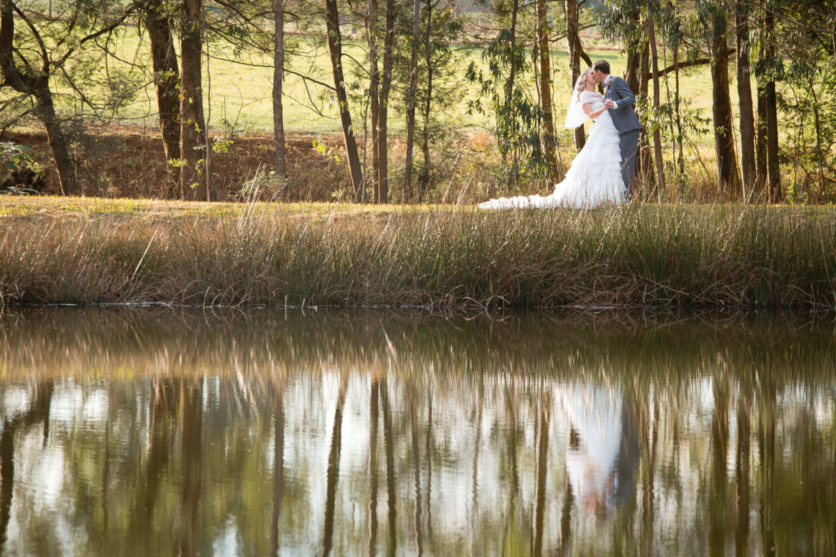 bride and groom over a lake at Cranford Country Lodge