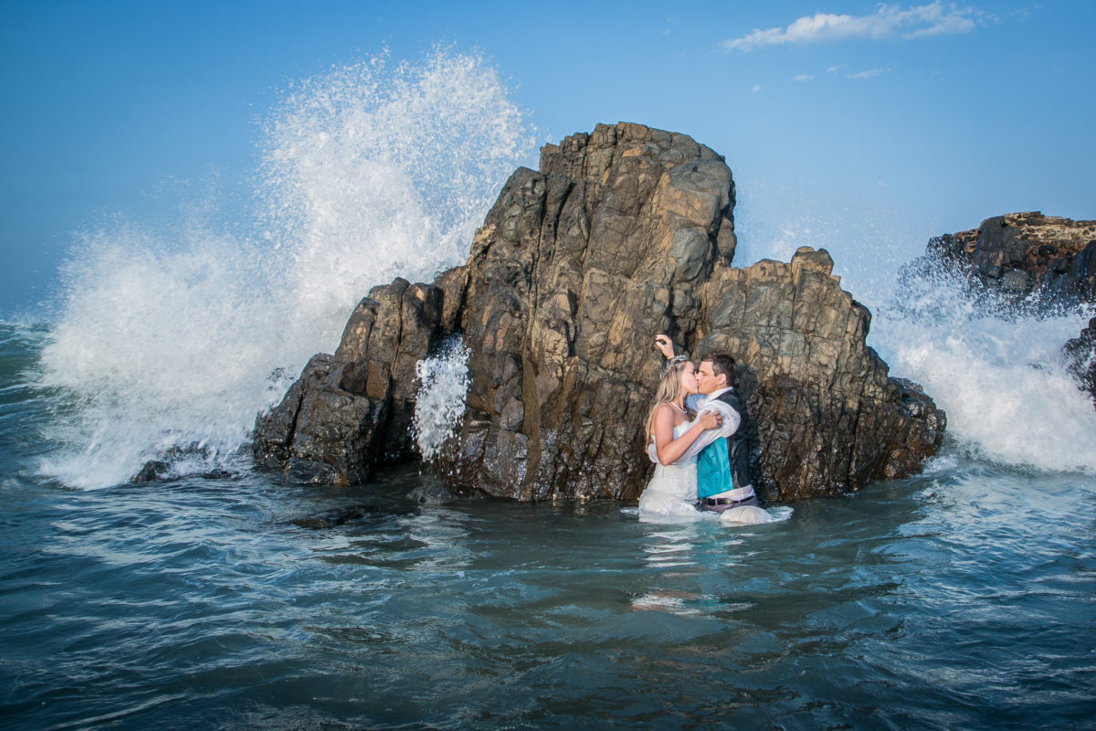 Standing in front of a rock with the waves hitting it for the gorgeous picture