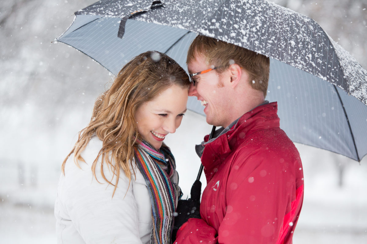 Under a snowy umbrella having a beautiful moment together in the midlands