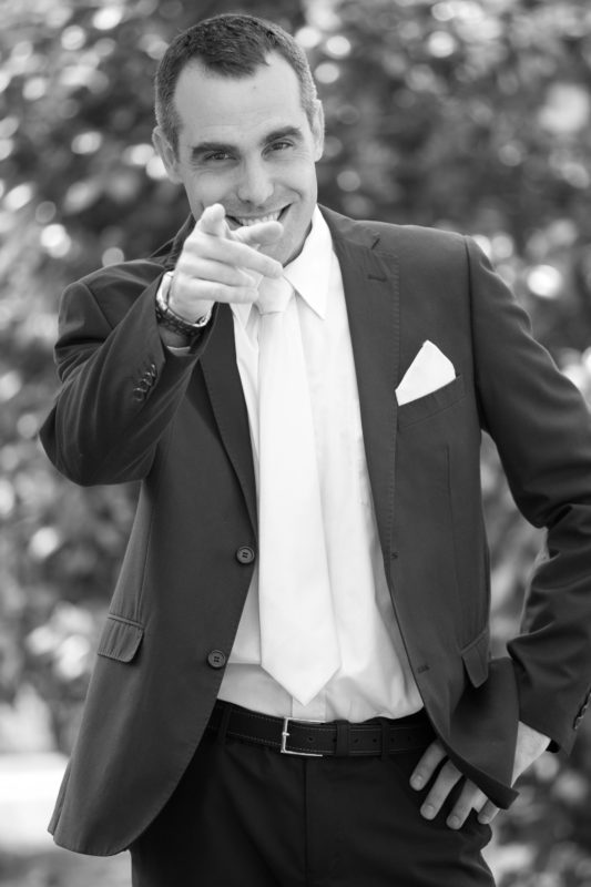 Groom in blank and white pointing with a grin