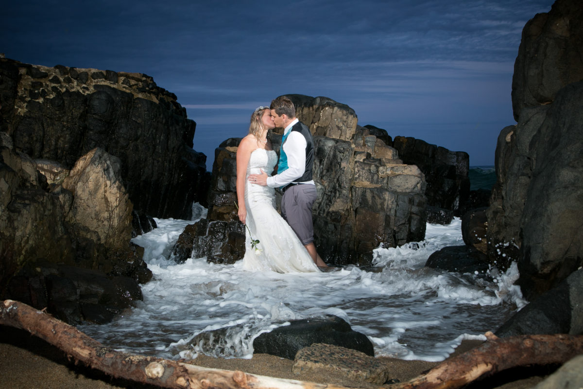 bride and groom kissing in the dramatic light