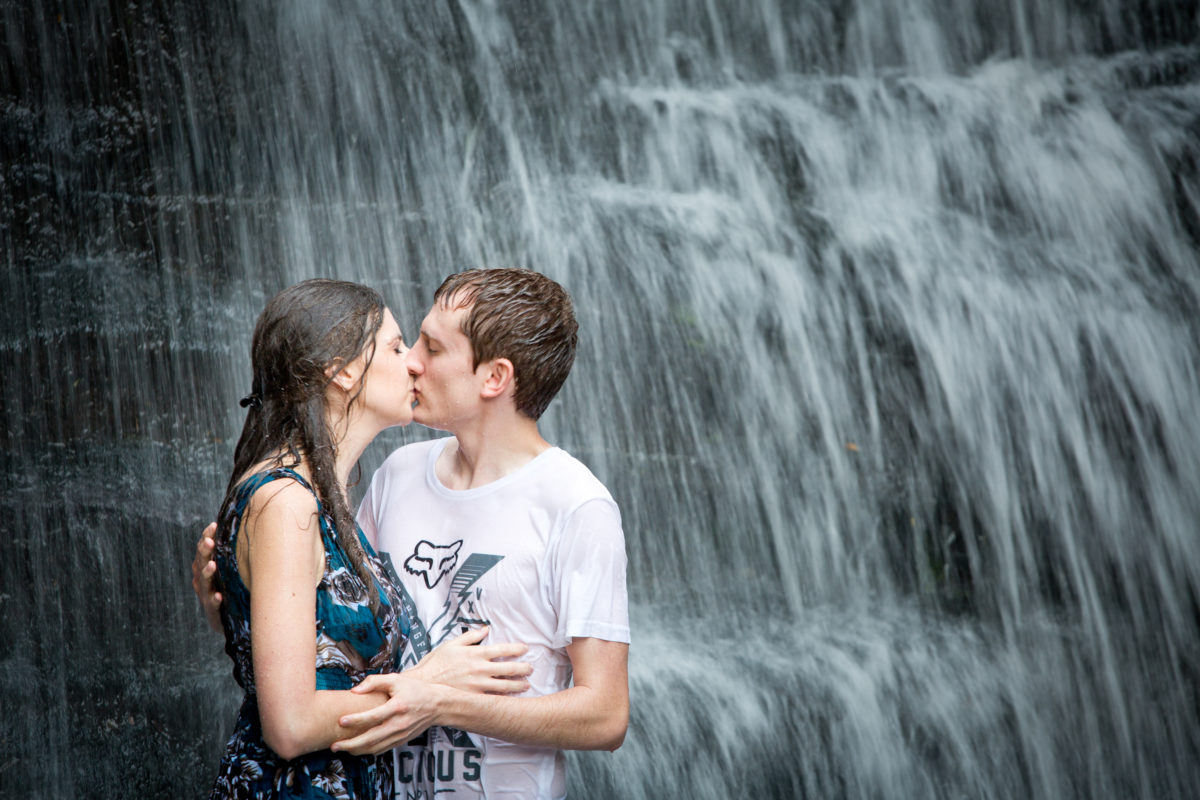 Kissing in front of a waterfall for their engagement shoot