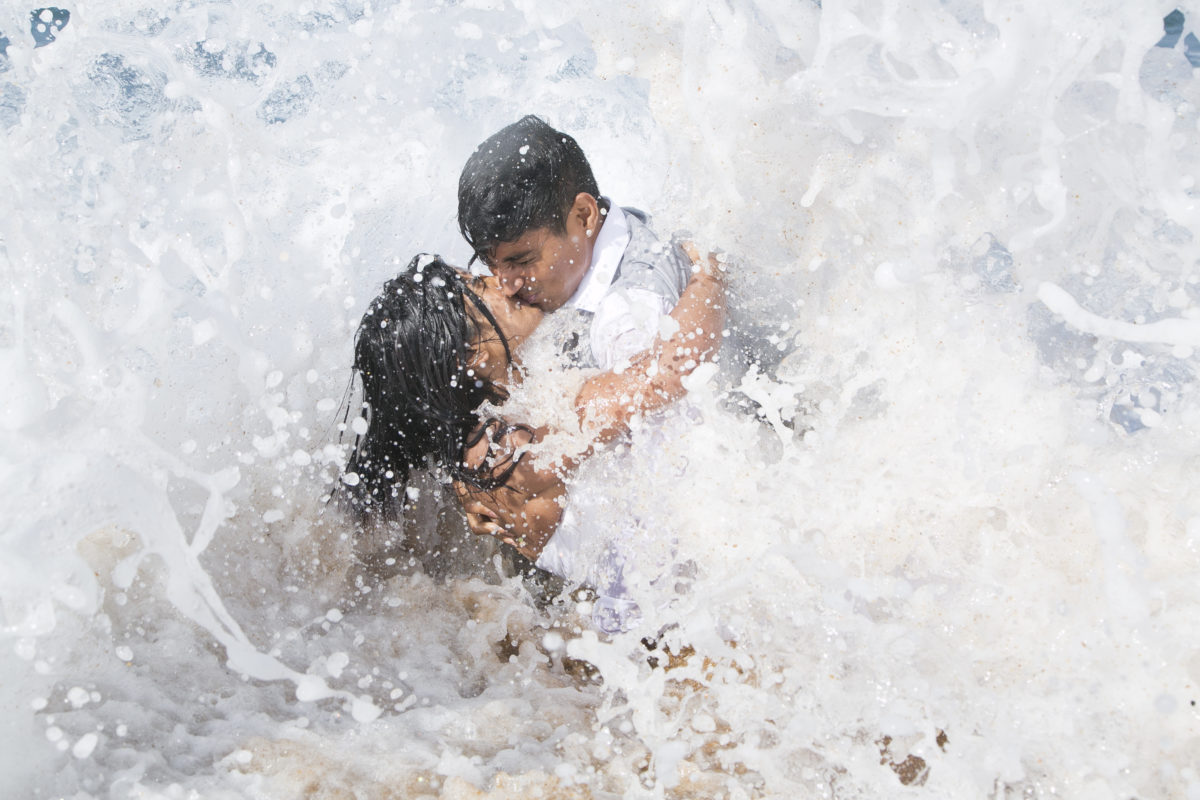 The bride and groom are engulfed beautifully by the wave