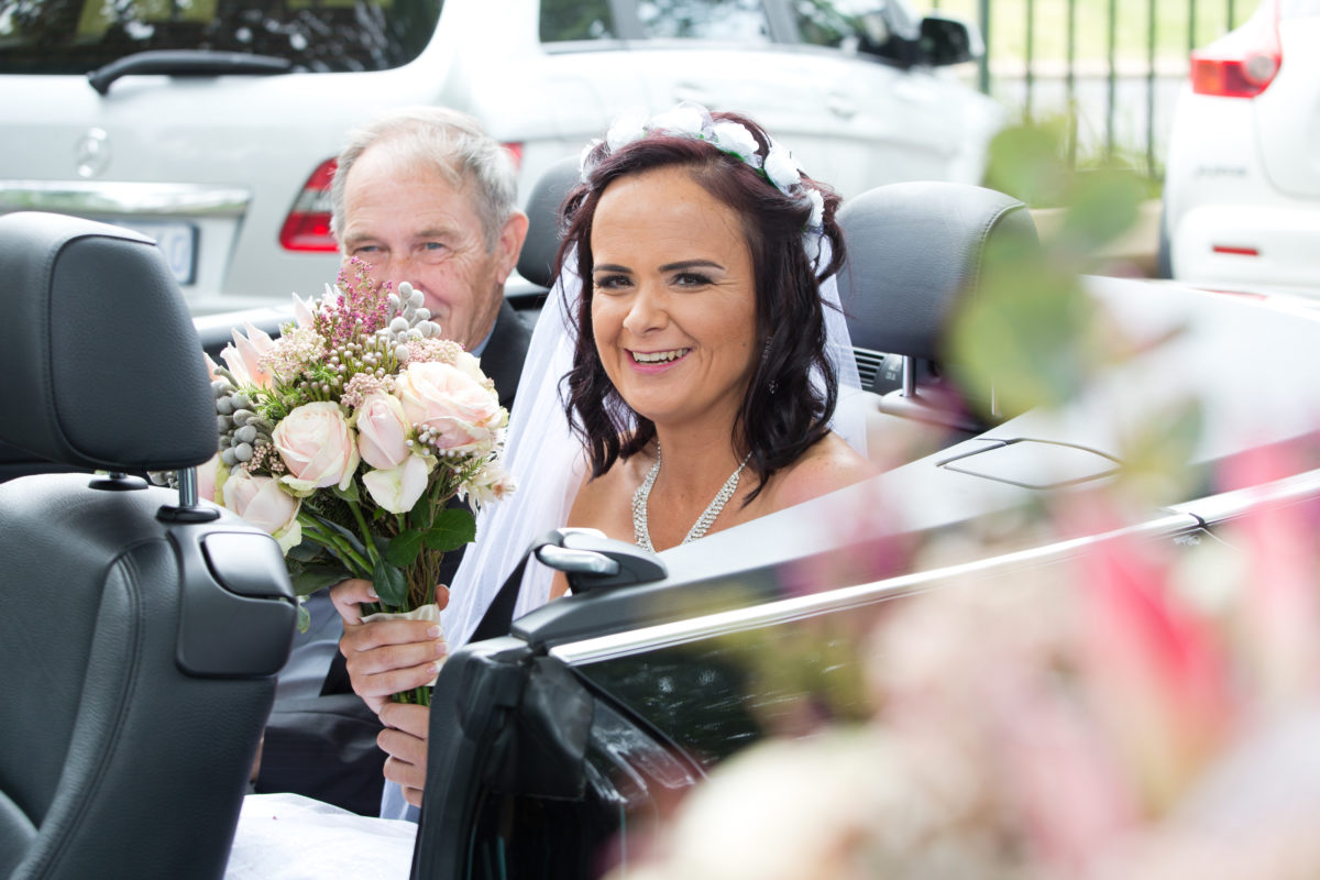 Bride arriving at the ceremony with her dad in the car with her