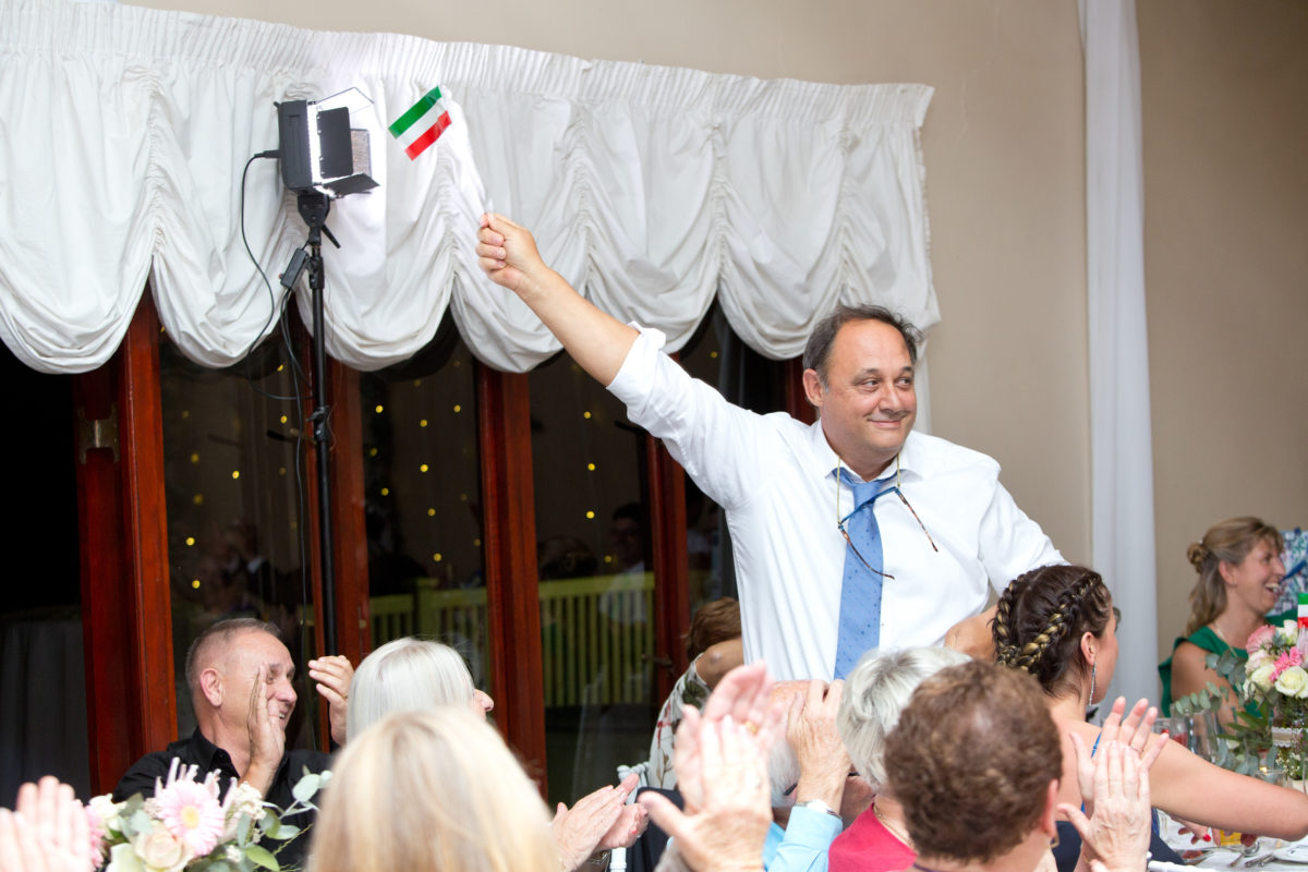 Uncle waving an Italian flag in the reception at Eden Lassie