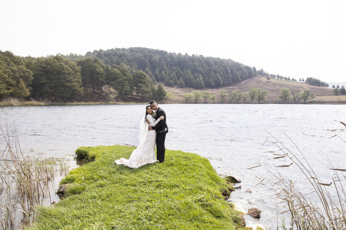 a bride and groom standing in front of a lake at a Waterwoods wedding