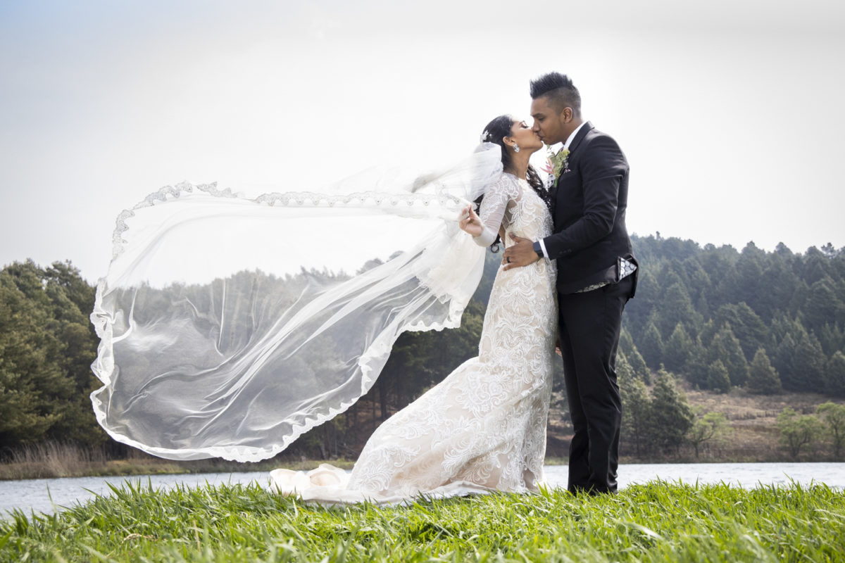 the bride letting her veil flow beautifully in the wind, whilst kissing her husband at a Waterwoods  wedding