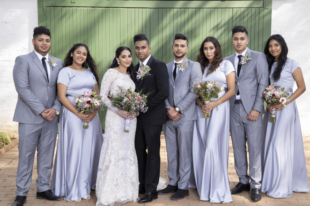the bridal party standing in front of a door at a Waterwoods wedding