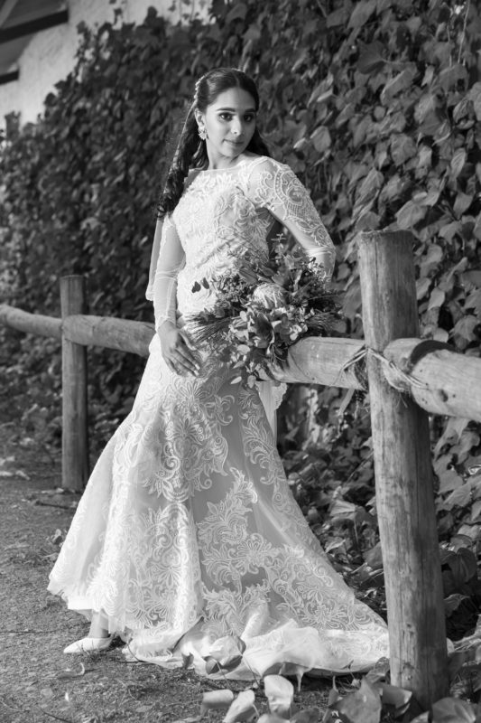 the bride leaning ahainst a small fence at Waterwoods wedding in the Midlands
