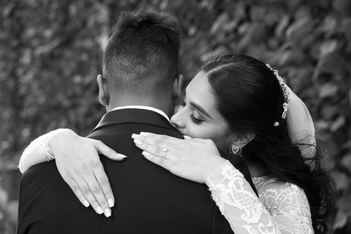 the bride kissing her husband on the shoulder at a Waterwoods  Wedding