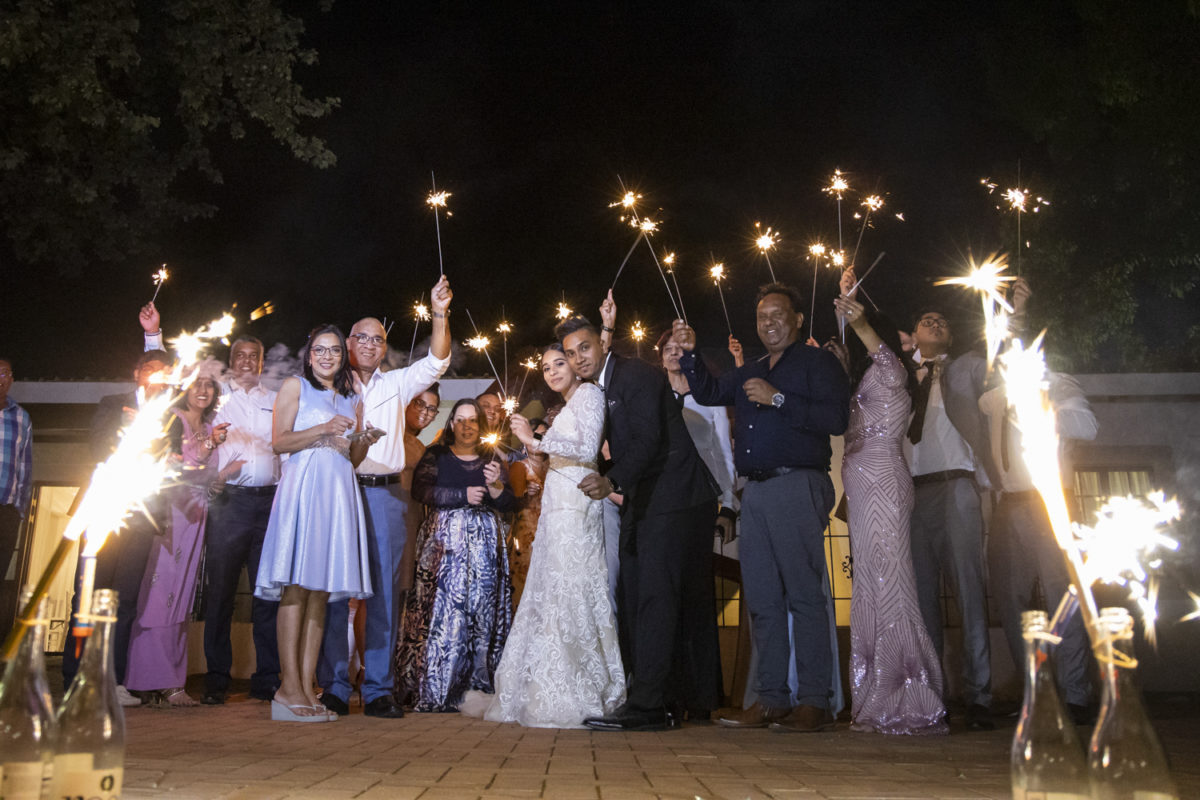 the bride and groom with their guest with sparkles around them at the Waterwoods wedding