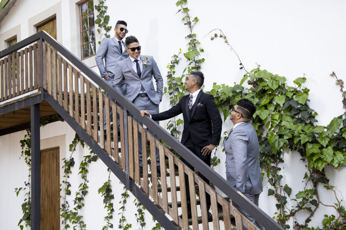 The groom and groomsmen chatting on a staircase at  a Waterwoods Wedding