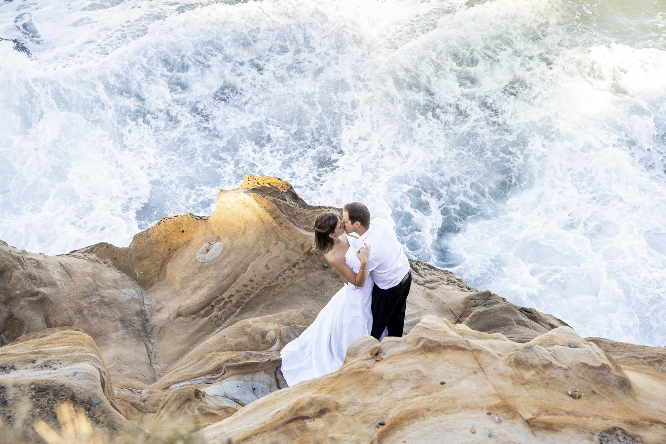 smokey water trash-the-dress bride and groom kissing overhead shot with the waves