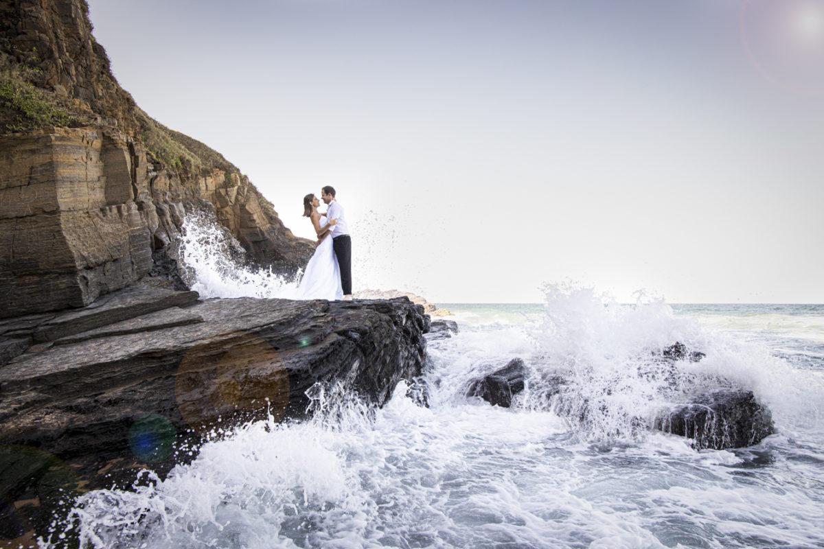 smokey water trash-the-dress waves crashing the rocks with bride and groom