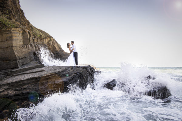 smokey water trash-the-dress waves crashing the rocks with bride and groom