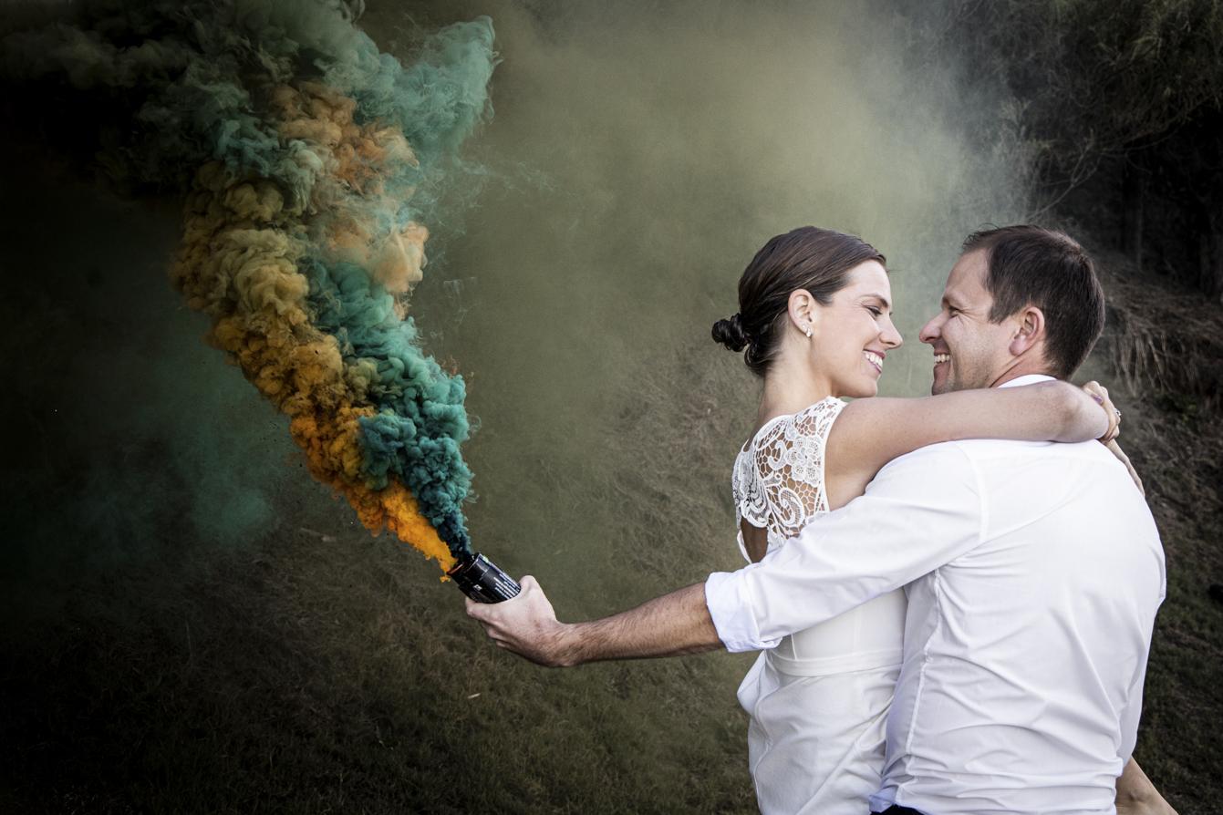 smokey water trash-the-dress bride and groom with smoke bombs