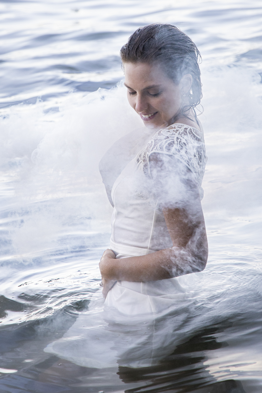 smokey water trash-the-dress bride in the water with smoke around her
