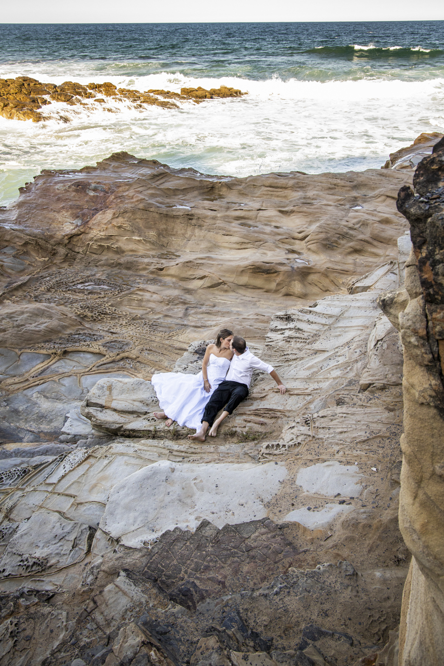 smokey water trash-the-dress high shot of the bride and groom sitting on the rocks