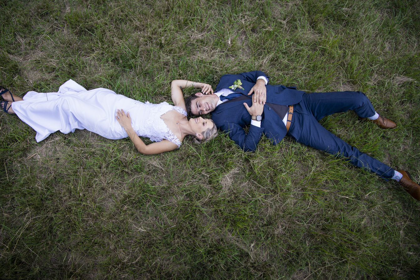Photographer at Gwahumbe wedding with bride and groom lying on the floor in the midlands